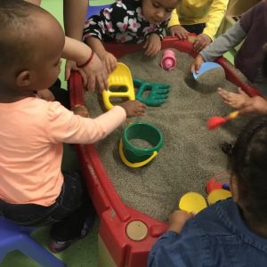 Daycare toddlers playing with sand