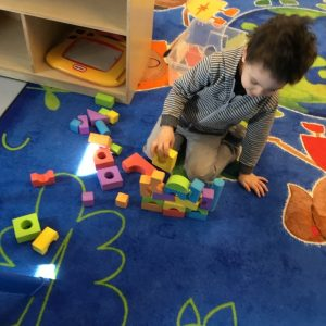 Daycare child playing with blocks